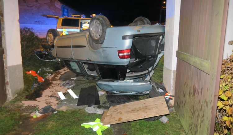 Auto zbořilo hradbu a přistálo na střeše ve vjezdu dalšího domu, řidič od nehody ujel jiným vozem