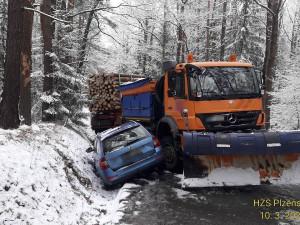 Na zledovatělé silnici havaroval kamion se dřevem, sypač i osobák