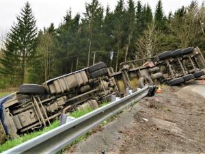 Kamion s nákladem dřeva nezvládl průjezd zatáčkou, položil se na bok a zřítil ze svahu